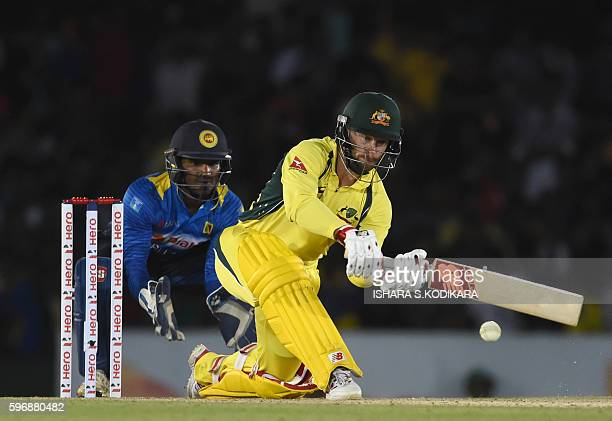 Australian cricketer Matthew Wade plays a shot as Sri Lankan wicketkeeper Kusal Perera looks on during the third One Day International cricket match...