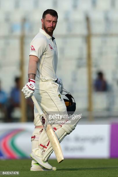 Australian cricketer Matthew Wade walks off the field after being dismissed by Bangladeshi cricketer Mustafizur Rahman during the third day of the...