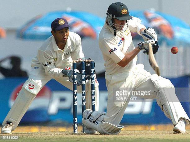 Australian cricketer Michael Clarke is watched by Indian wicketkeeper Parthiv Patel as he plays a sweep shot during the fourth day of the third Test...