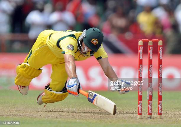 Australian cricketer Michael Hussey dives to save his wicket from a run out attempt by West Indies cricketer during the third-of-five One Day...