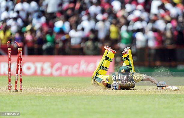 Australian cricketer Michael Hussey dives to save his wicket from a run out attempt by West Indies players during the third-of-five One Day...