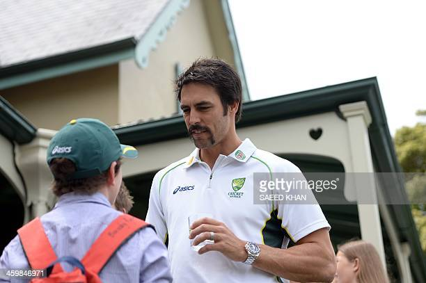 Australian cricketer Mitchell Johnson talks to a child during a New Year's Day reception hosted by the Australian Prime Minister Tony Abbott for...