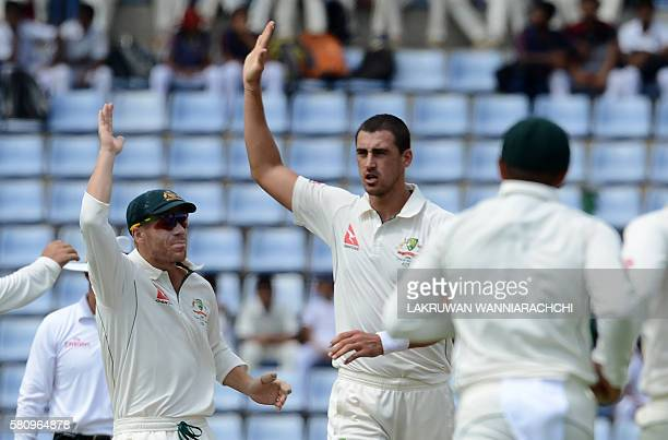 Australian cricketer Mitchell Starc celebrates with his teammates after he dismissed Sri Lankan batsman Dimuth Karunaratne during the first day of...
