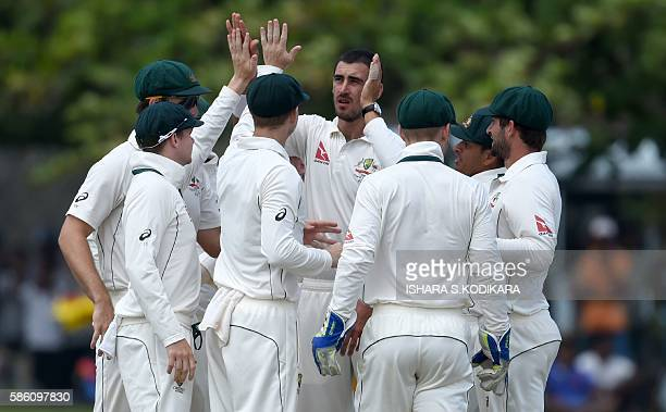 Australian cricketer Mitchell Starc celebrates with teammates after he dismissed unseen Sri Lankan batsman Dimuth Karunaratneduring the second day of...