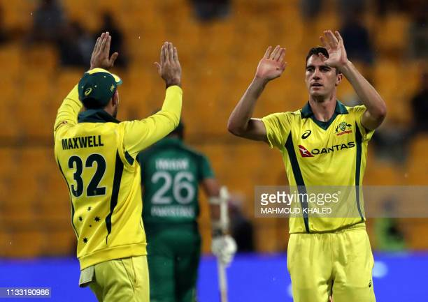 Australian cricketer Patrick Cummins celebrates with his teammate the dismissal of Pakistani cricketer Haris Akmal during the third one day...