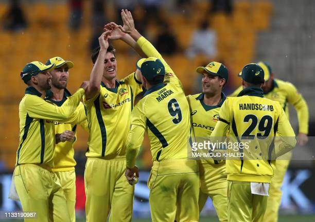 Australian cricketer Patrick Cummins celebrates with his teammates the dismissal of Pakistani cricketer Haris Akmal during the third one day...