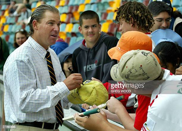 Australian cricketer Shane Warne , who finishes a 12 month drug ban on 10 February 2004, signs autographs for eager fans, as rain delays the start of...