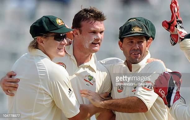 Australian cricketer Shane Watson and captain Ricky Ponting congratulate teammate Doug Bollinger for taking the wicket of Indian cricketer Sachin...