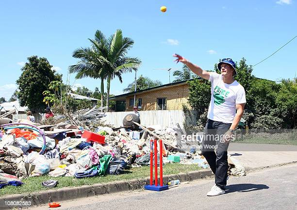 Australian cricketer Shane Watson joins in a game of street cricket with local children in the suburb of Ipswich on January 17 2011 in Brisbane...