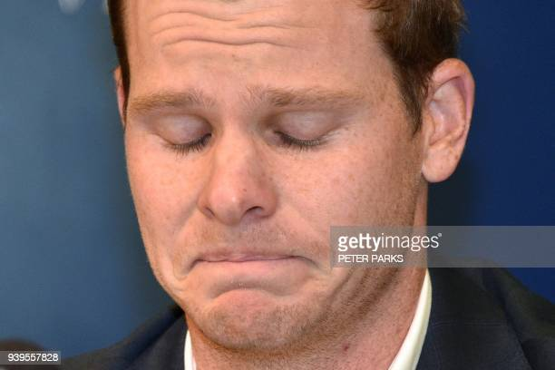 TOPSHOT Australian cricketer Steve Smith reacts at a press conference at the airport in Sydney on March 29 after returning from South Africa...