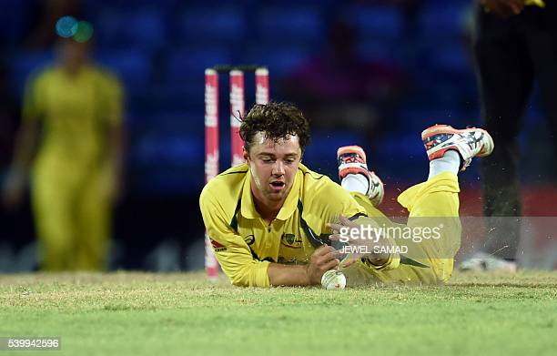 Australian cricketer Travis Head dives to stop a shot by West Indies batsman Marlon Samuels hits a boundary off Australian bowler Mitchell Marsh...