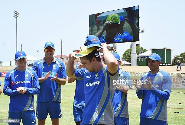 Australian cricketer Travis Head wears his official cricket team One Day International as his teammates applaud before the start of the Trination...