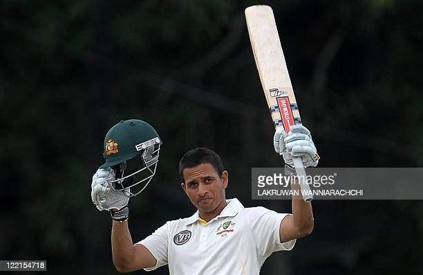 Australian cricketer Usman Khawaja raises his bat and helmet in celebration after scoring a century during the second day of a threeday practice...
