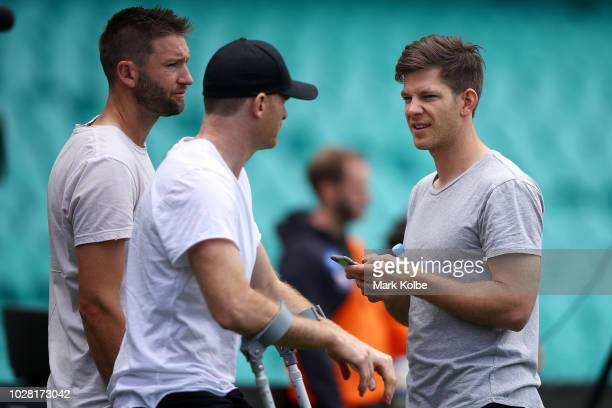 Australian cricketers Andrew Tye and Tim Paine speak to Heath Shaw as they watch on during a Greater Western Sydney Giants AFL training session at...