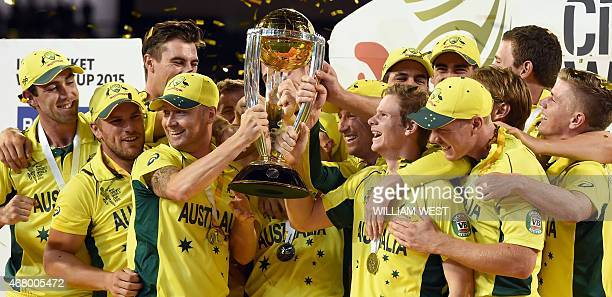 Australian cricketers celebrate with the trophy after the winning the 2015 Cricket World Cup final between Australia and New Zealand in Melbourne on...