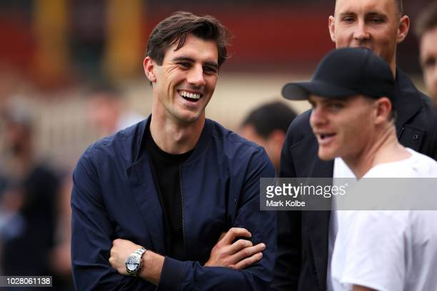 Australian cricketers Pat Cummins and Billy Stanlake speak to Heath Shaw as they watch on during a Greater Western Sydney Giants AFL training session...