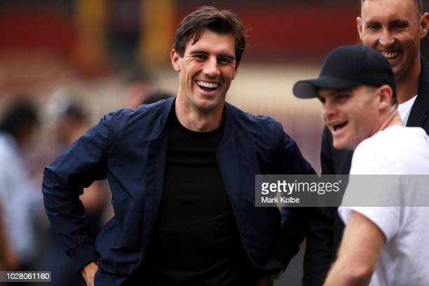 Australian cricketers Pat Cummins and Billy Stanlake speak to Heath Shaw share a laugh as they watch on during a Greater Western Sydney Giants AFL...