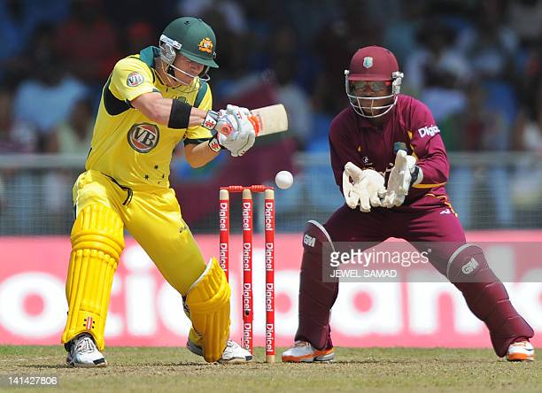 Australian crickter David Warner plays a shot as West Indies wicketkeeper Carlton Baugh looks on during the firstoffive One Day International matches...