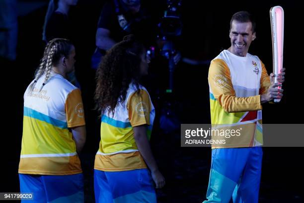 Australian cyclist cyclist Brad McGee carries the Queen's Baton in the opening ceremony of the 2018 Gold Coast Commonwealth Games at the Carrara...