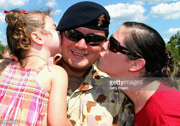 Australian Defence Force soldier Lance Corporal Glen Miles is kissed by wife Nikki and threeyearold daughter Abbey after a parade to farewell 450...