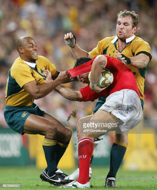 Australian defenders George Gregan and Rocky Elsom tackle Welsh halfback Mike Phillips during their second rugby Test match in Brisbane 02 June 2007...