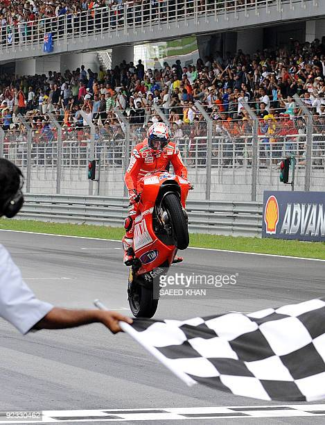 Australian Ducati Marlboro rider Casey Stoner celebrates his race victory at the finish line of the Malaysian Motocycle Grand Prix at the Sepang...