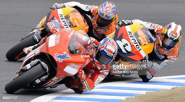 Australian Ducati rider Casey Stoner leads against Spanish rider Dani Pedrosa and Nicky Hayden of the US in the first lap of the MotoGP Japanese...