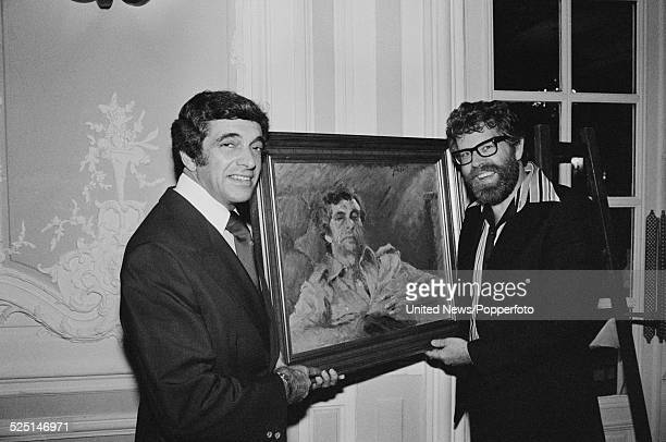 Australian entertainer and artist Rolf Harris presents English singer Frankie Vaughan with a portrait of his likeness in London on 12th October 1978