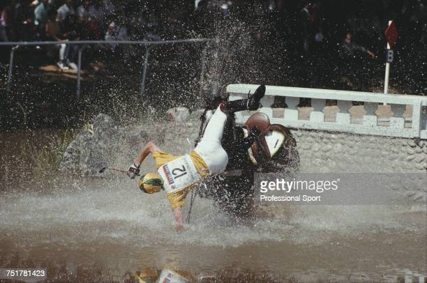 Australian equestrian Scott Keach pictured in action for the Australia team falling from his horse 'Trade Commissioner' at the water jump during...