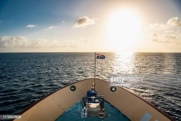 australian exploration vessel heading into the setting sun - schiffsbug stock-fotos und bilder