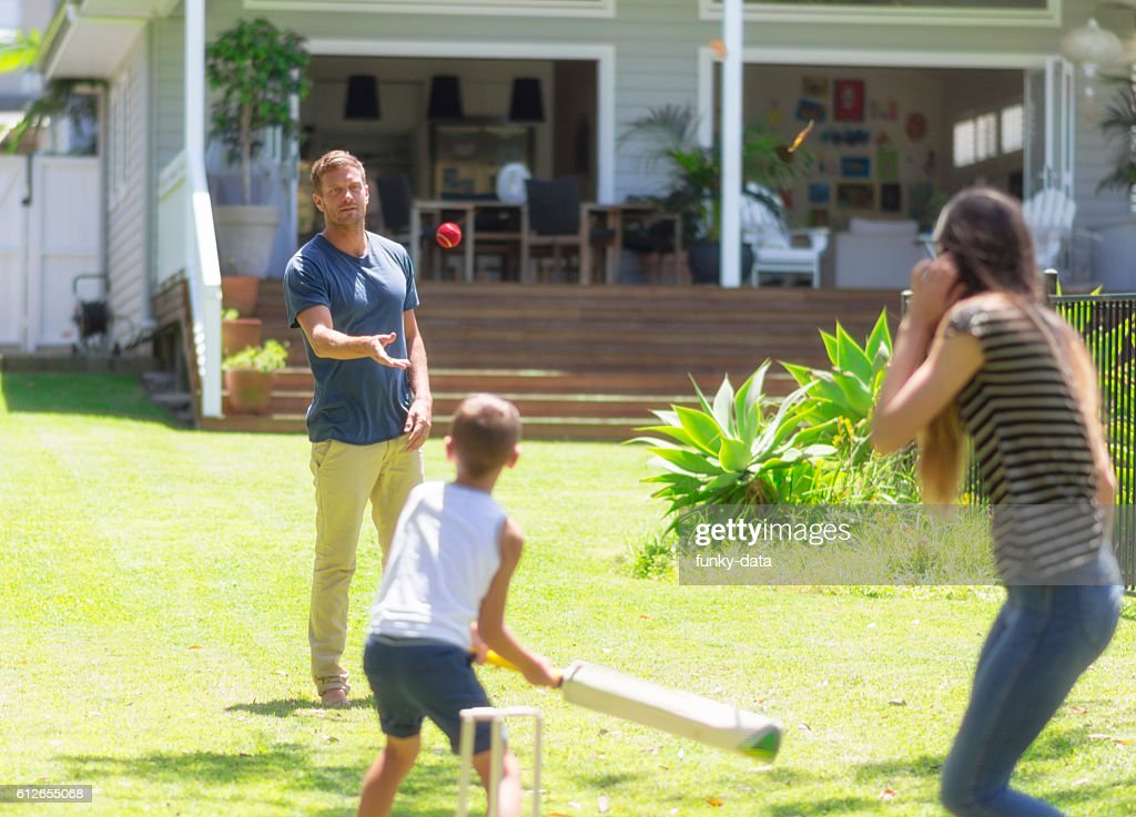 Australian family playing cricket : Stock Photo