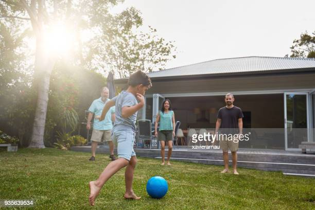 australian family playing in the back yard garden - kicking stock pictures, royalty-free photos & images