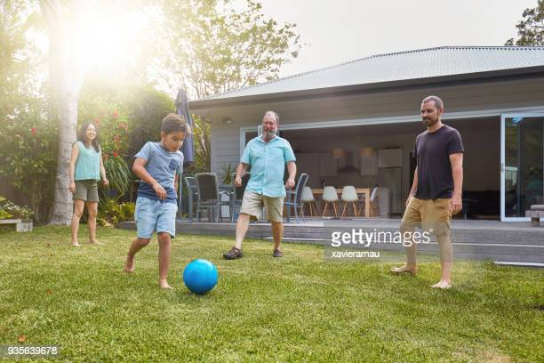 Australian family playing soccer in the back yard garden at sunset