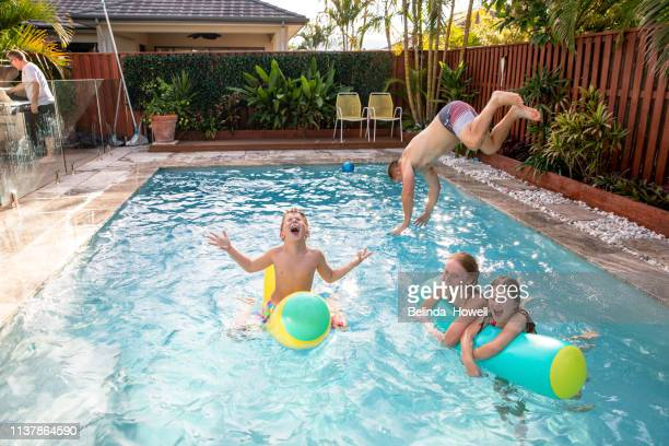 Australian family plays in swimming pool on a warm autumn afternoon