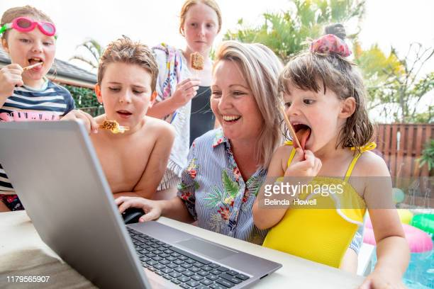 Australian family use a desktop devices together on the back deck whilst eating icecream.