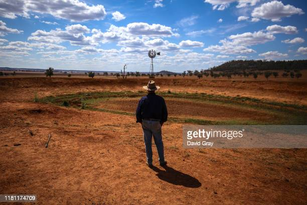 Australian farmer Ash Whitney looks across at a windmill that stands next to a dried-up dam on his drought-affected property located in the Goolhi...