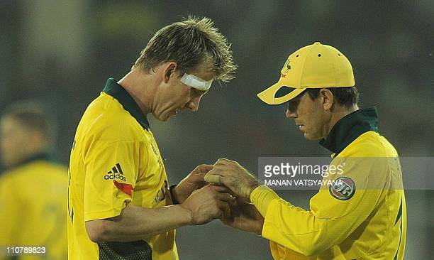 Australian fast bowler Brett Lee talks with captain Ricky Ponting during the quarterfinal match of The ICC Cricket World Cup 2011 between India and...