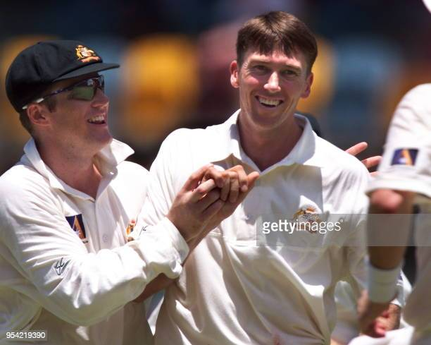 Australian fast bowler Glenn McGrath is congratulated by his captain Mark Taylor after McGrath captured six English wickets on the fouth day of the...