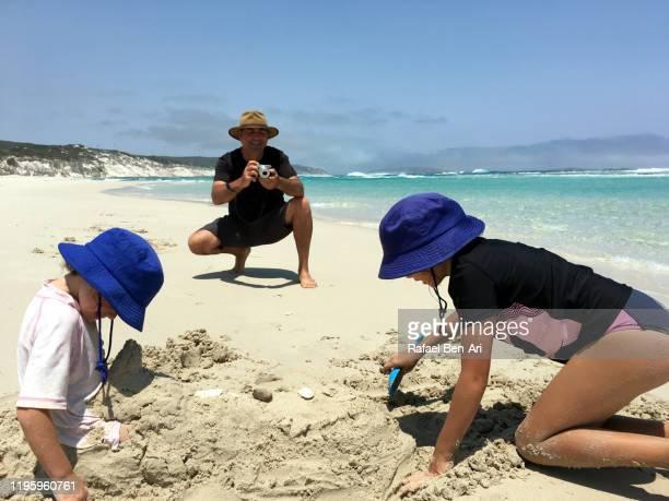 australian father photographing his daughters having fun on the beach - rafael ben ari fotografías e imágenes de stock
