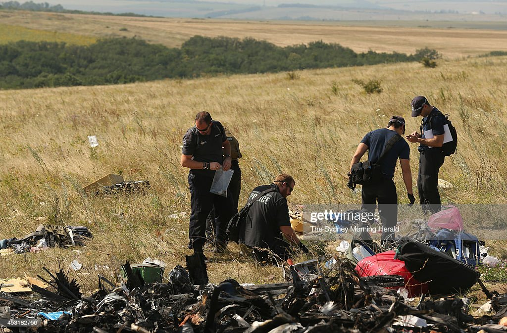 Australian Federal Police officers and their Dutch counterparts collect human remains and personal belongings from the MH17 Malaysian Airlines crash site in the fields outside the village of Grabovka, Eastern Ukraine, August 2, 2014. (Photo by Kate Geraghty/The Sydney Morning Herald/Fairfax Media via Getty Images).