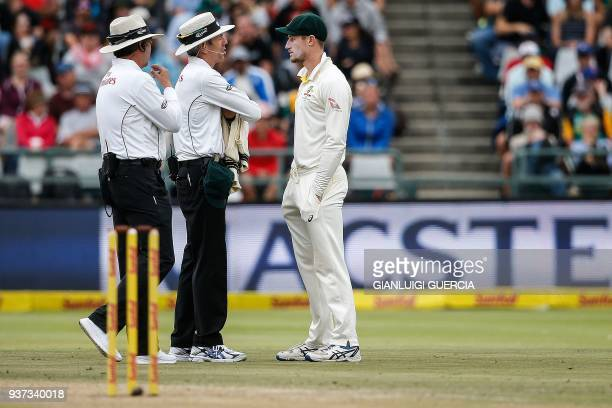TOPSHOT Australian fielder Cameron Bancroft is questioned by Umpires Richard Illingworth and Nigel Llong during the third day of the third Test...