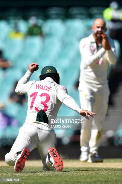 Australian fielder Matthew Wades takes a successful catch to dismiss Indian captain Ajinkya Rahane as Australian Nathan Lyon celebrates during day...