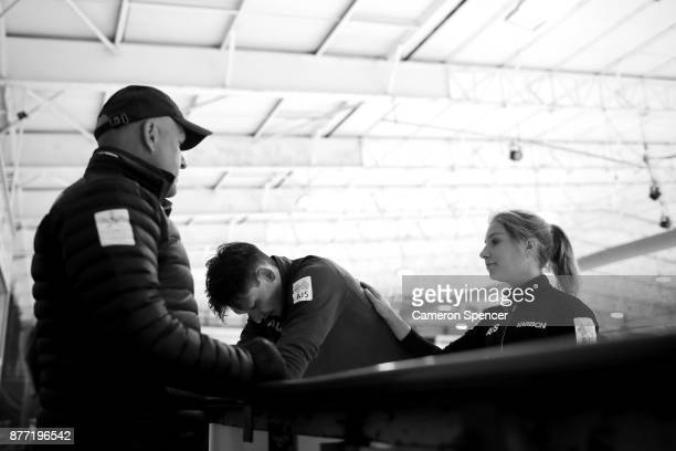 Australian figure skater Harley Windsor and his skating partner Ekaterina Alexandrovskaya talk to their coach Andrei Pachin during a training session...