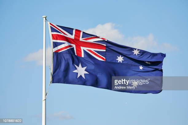 australian flag flying in the wind with blue sky - australian politics stock pictures, royalty-free photos & images
