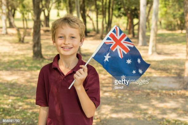 australian flag waving by primary school boy student for australia day - australian flag stock pictures, royalty-free photos & images