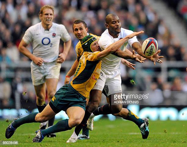 Australian fly half Matt Giteau stretches for the ball against England's Full Back Ugo Monye during the Investec Challenge Series International rugby...