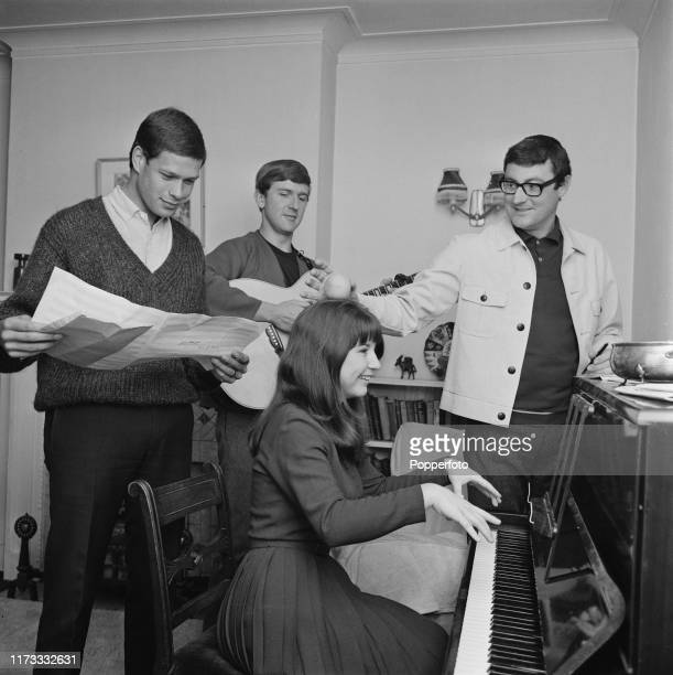 Australian folk group The Seekers rehearse at and around a piano at their home in London in July 1966; Members of The Seekers are, from left, Keith...