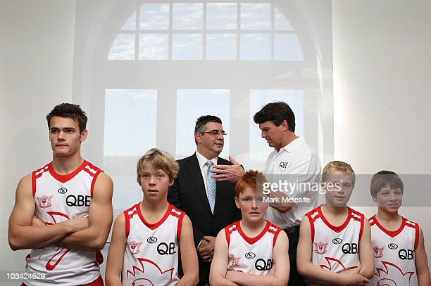 Australian Football League CEO Andrew Demetriou and Swans Coach Paul Roos chat as Swans Academy players pose during a Sydney Swans AFL media...