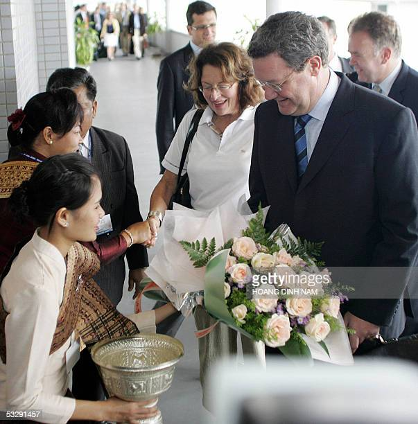 Australian Foreign Minister Alexander Downer and his wife Nicky are greeted with flowers by Lao women upon their arrival at Vientiane's Wattay...