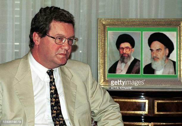 Australian Foreign Minister Alexander Downer, seated near photos of Iran's Supreme Leader Ali Khamenei and his predecessor Ayatollah Ruhollah...
